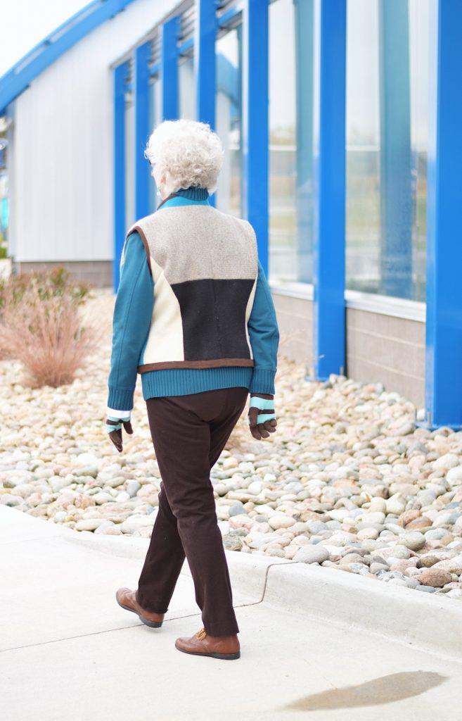 Layering a short vest over a jacket for older women
