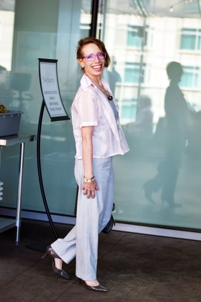 wearing a sheer pink top over a grey jumpsuit