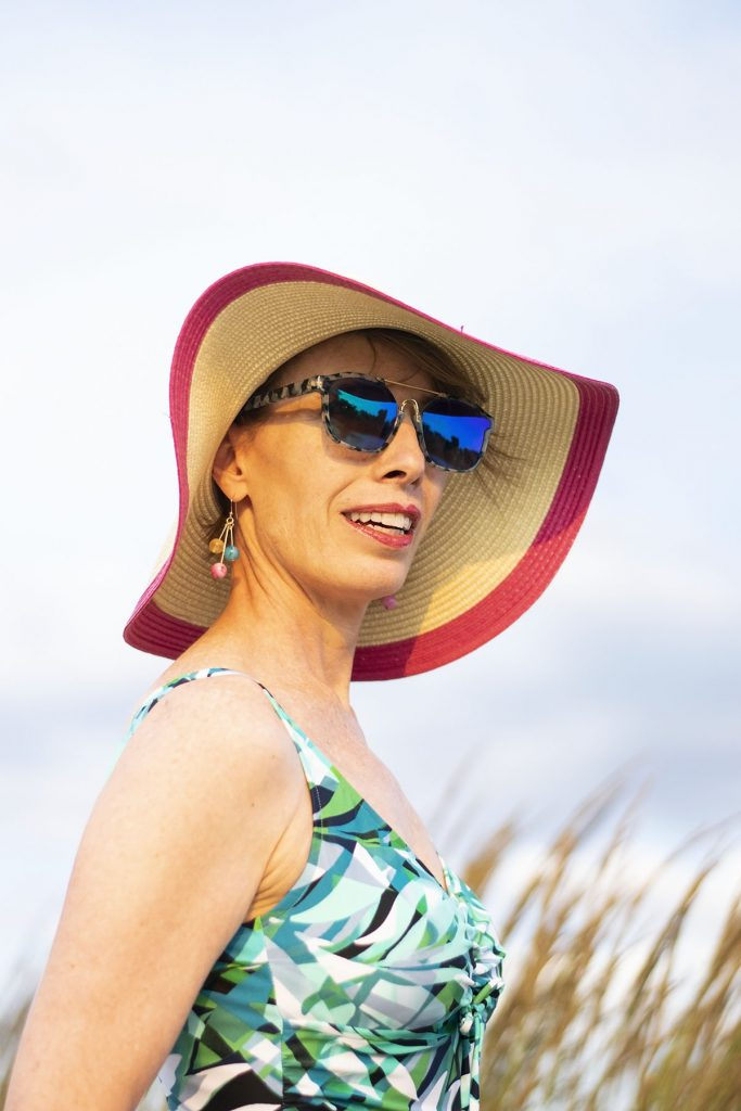 What to wear to the beach for women over 50 including a sun hat