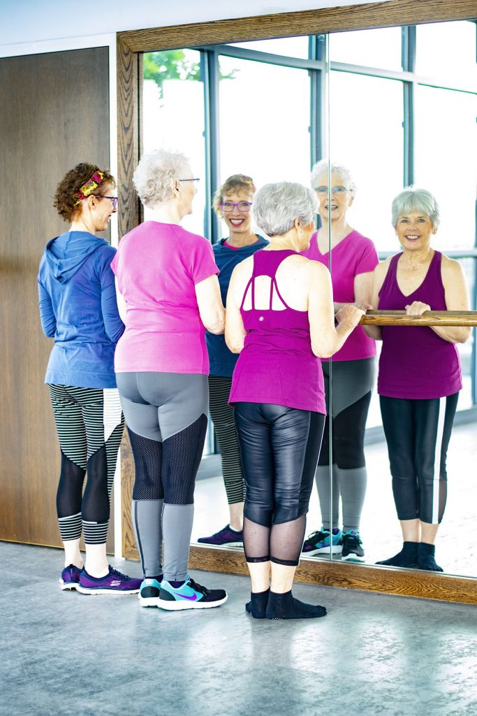 New fitness clothes for women over 50 working out at a barre
