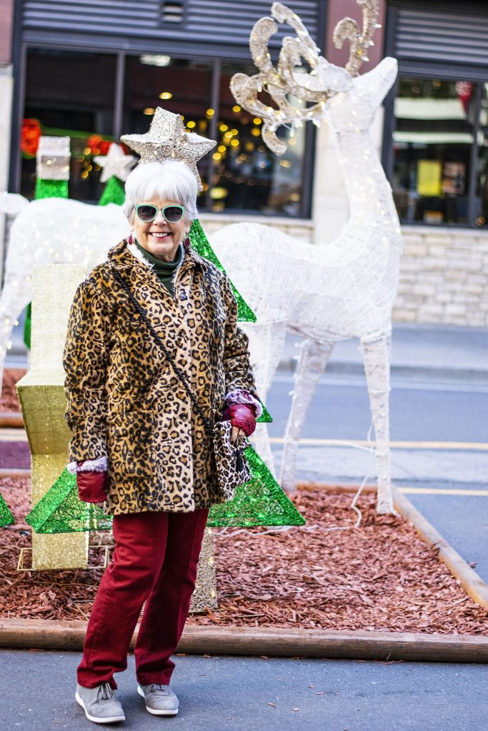 Woman over 70 styling a leopard print coat