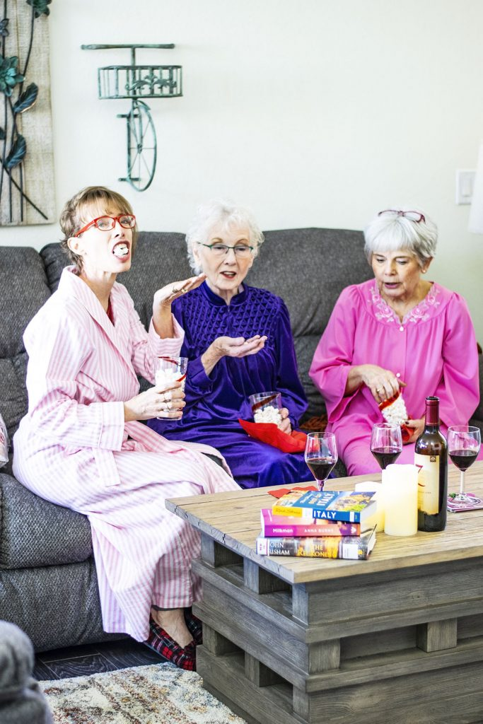 Women's robes and slippers with popcorn and wine