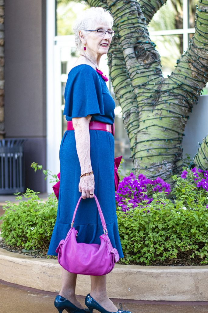 Woman over 70 showing how to accessorize a blue dress