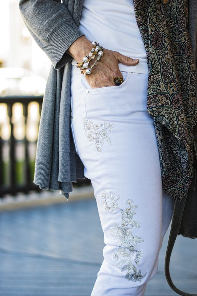 Embroidery on white jeans with a magnetic scarf clasp