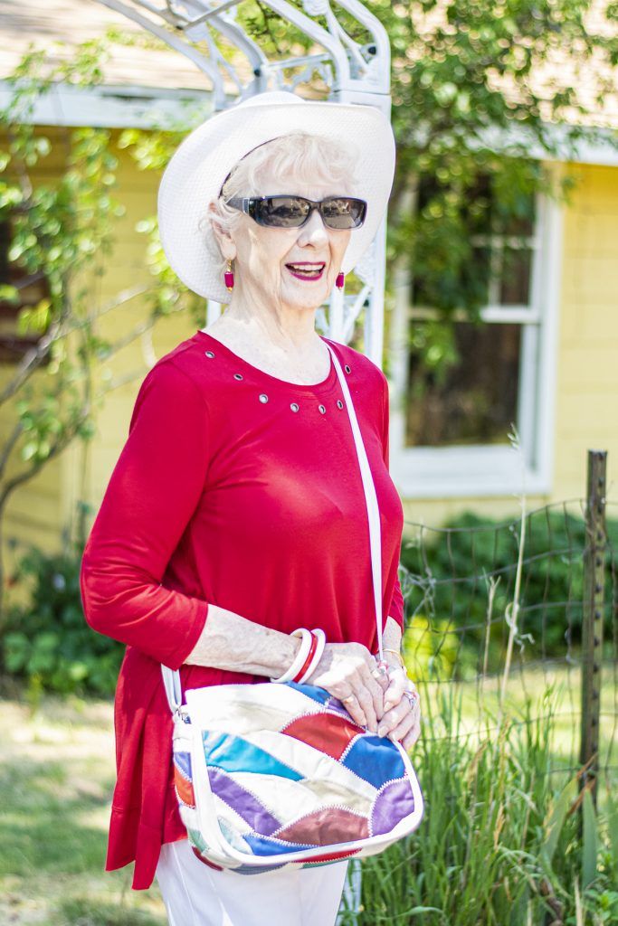 Red grommet top with white pants
