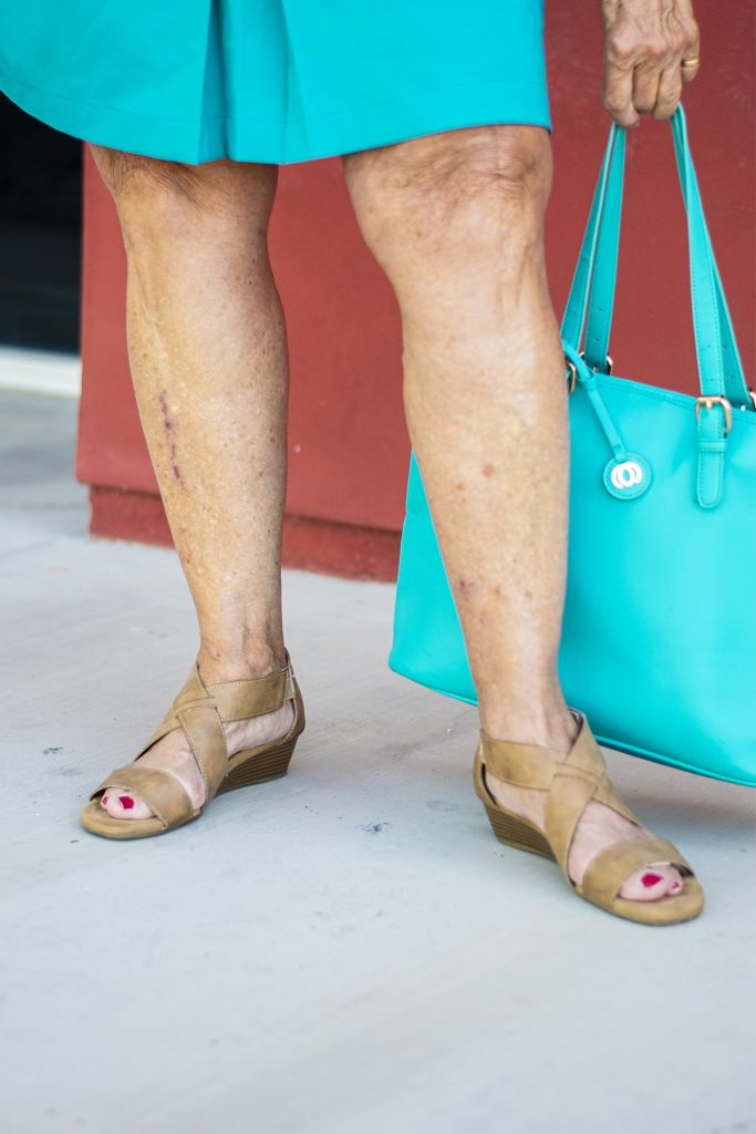 Nude shoes with a turquoise skirt and showing legs