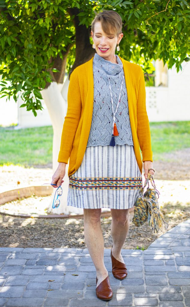 Mustard cardigan wearing a summer dress in winter