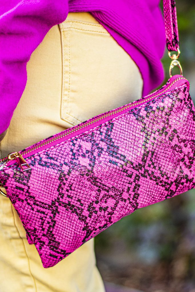 Pink snakeskin purse as part of neon pink sweater outfit
